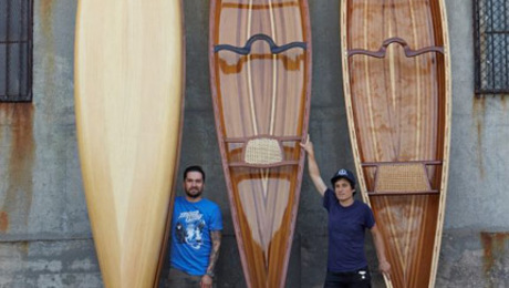 L-R: Offerman Woodshop's Mike Flores and Lee Rh standing amid a stack of canoes.