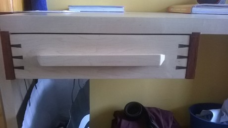 Front drawer of the table is from a solid piece of Maple. Routed down to create the handle. Keying is done with Ebony.
