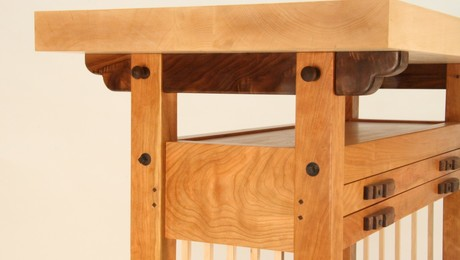 The table's joinery design allows it to be disassembled. The 3 inch maple top can be removed by pulling the the walnut pins in the bridle joints at the top of the legs. The 4 bed bolts on either side allow the frame to also be disassembled.