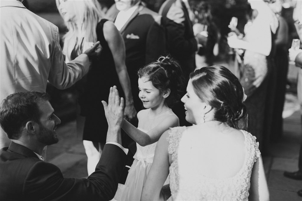 bride and groom candid moment with flower girl at greenville country club wedding