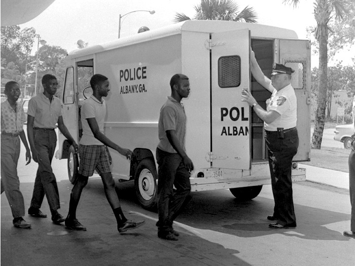 Four black protesters are loaded into a police wagon