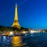 View of the Eiffel Tower at night from a Seine river cruise in Paris, France