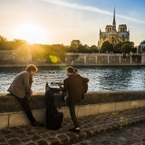 Street musicians by the Seine at sunset, overlooking Notre-Dame in Paris, France