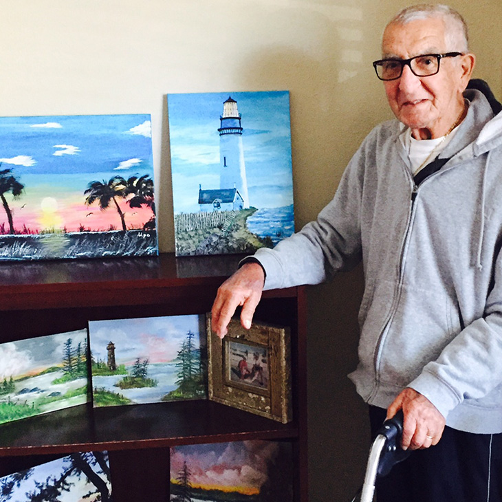 Monday Motivation resident with paintings of the beach next to him