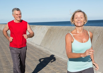 woman jogging in front of man by the ocean