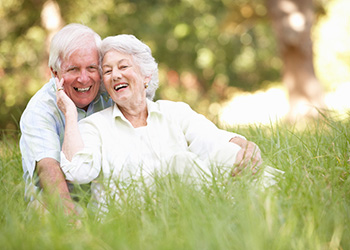 woman touching man's cheek while sitting on the grass