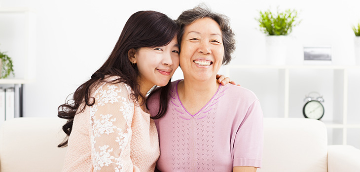 younger woman with arm around shoulder of elderly woman