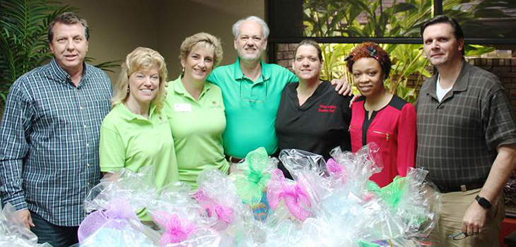 staff members with stuffed easter baskets to donate