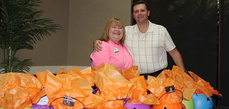 staff members with stuffed toy pumpkins to donate