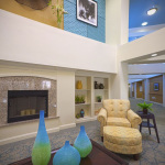 2 story waiting area with fireplace and artwork on walls