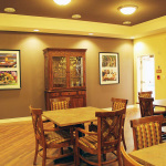 small dining area with 4 seat tables and artwork on walls