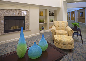 sitting area with fireplace and overstuffed chair and ottoman