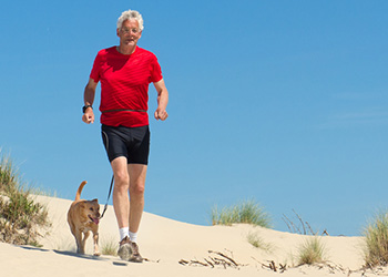 man in red shirt taking a jog on the beach with his dog