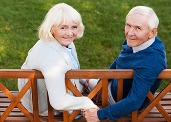 elderly couple holding hand on a bench and smiling