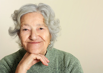 elderly woman in sweater with chin on hand