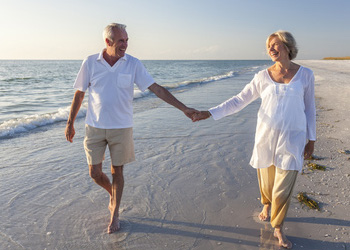 couple smiling and holding hands on the beach