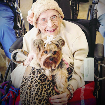 Doris smiling with small dog on her lap