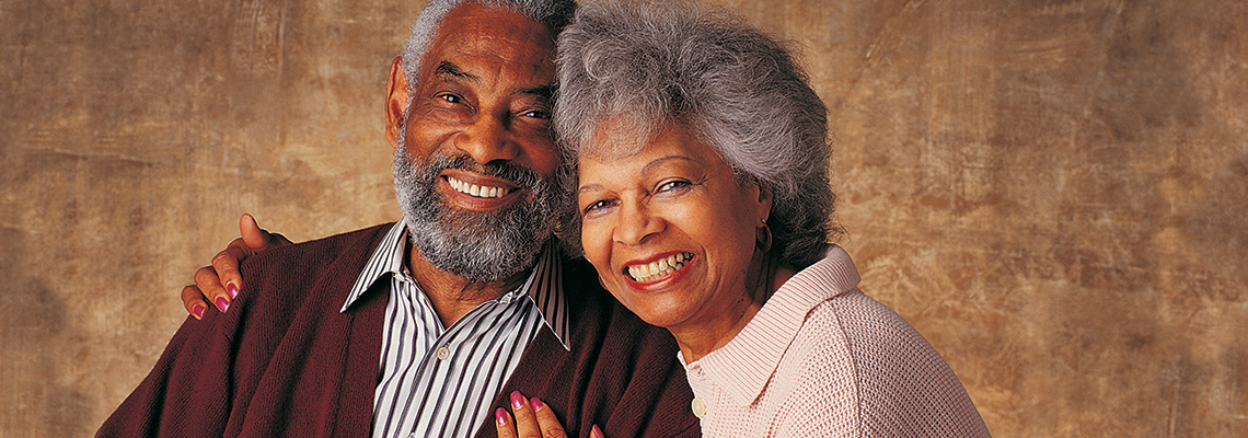 smiling couple with their heads tilted together
