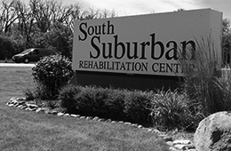 South Suburban sign surrounded by rocks and lush grass and bushes
