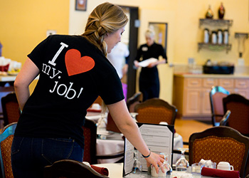 Staff member setting the table with a shirt on that says 'I love my job'