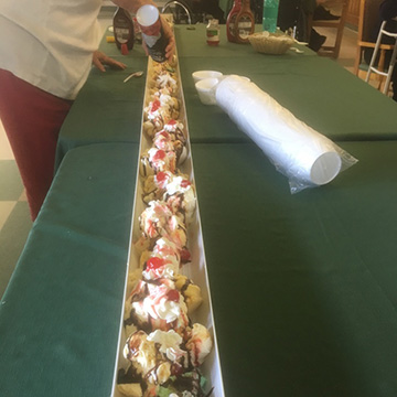 Two staff members setting up a large ice cream sundae station for residents