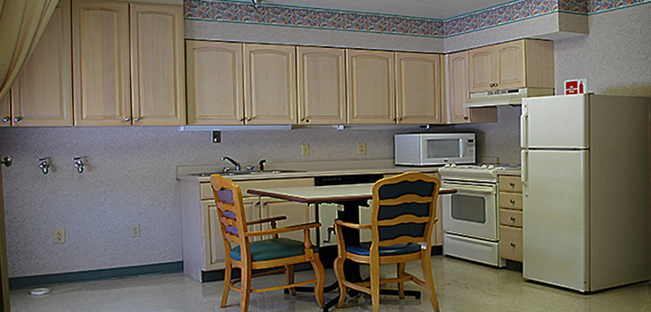Rehabiliation kitchen with stove, refrigerator, cupboards, microwave and dining area