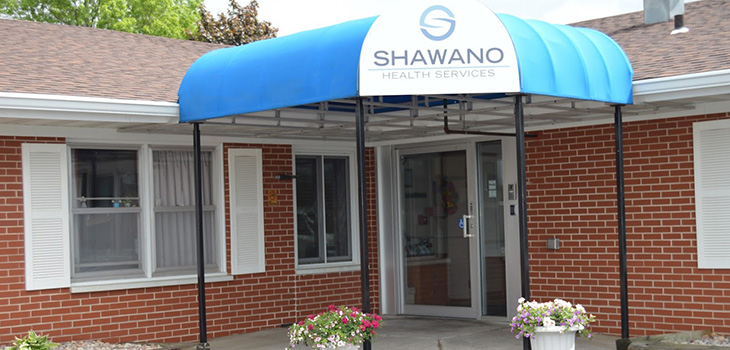 Entrance and front door of the building with a sign above that reads Shawano Health Services