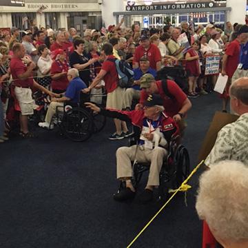 Cheering visitors inside ropes cheer on veterans
