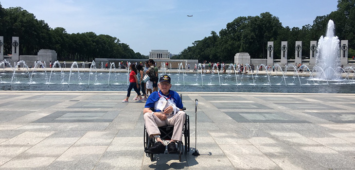 Richard in a wheelchair in front of a large water fountain