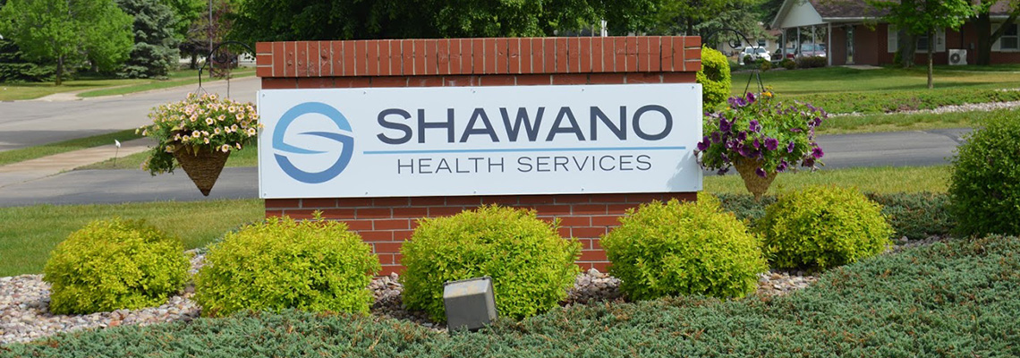 Shawano Health Services sign out front on a brick wall with hanging plants beside it