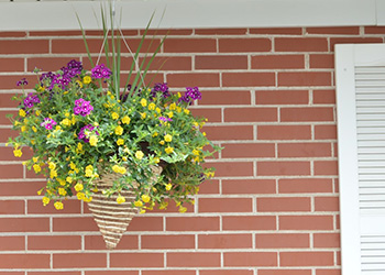 A wicker planter with bright flowers in bloom