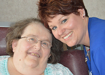 Resident and nurse smiling together