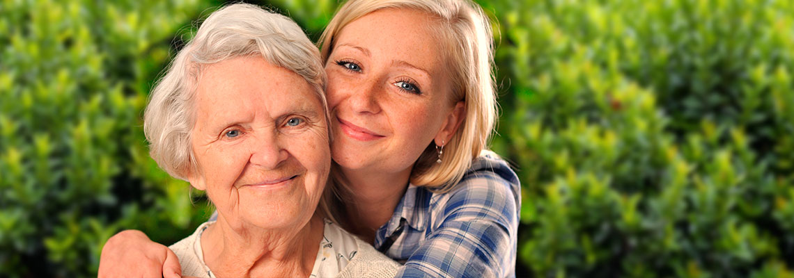 A grandmother and granddaughter embracing each other with lush greenery in the background