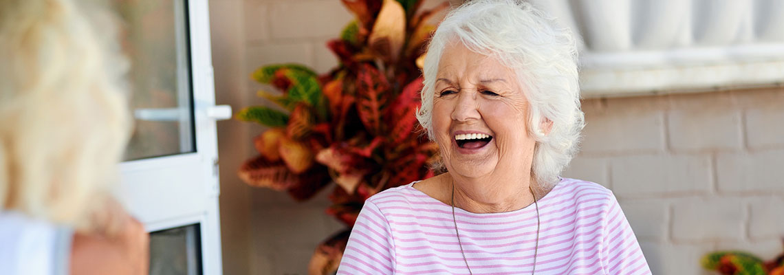 An elderly woman sitting outside laughing with another woman