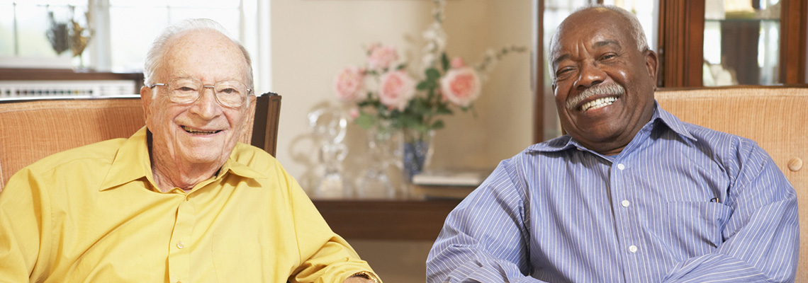 Two men sitting beside each other smiling in a home-like setting