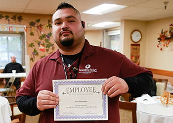 Employee of the month holding an award