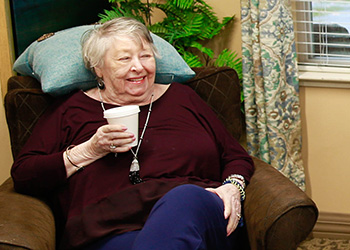 Resident enjoying a cup of coffee in a comfortable chair