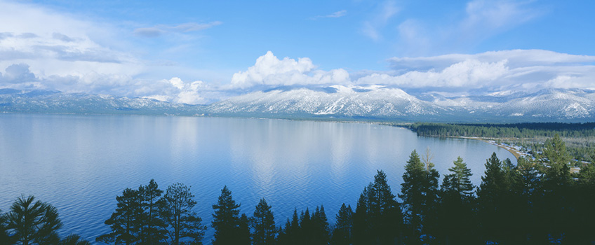 Beautiful mountains with a blanket of snow behind a large lake bordered with trees