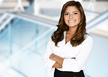 Business professional standing with her arms folded in front of her