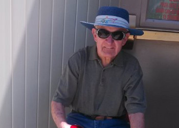 A resident sitting outside with sunglasses and a hat on