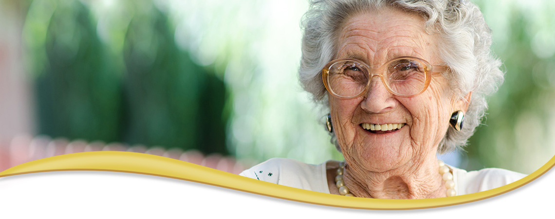 elderly smiling woman wearing glasses and pearls