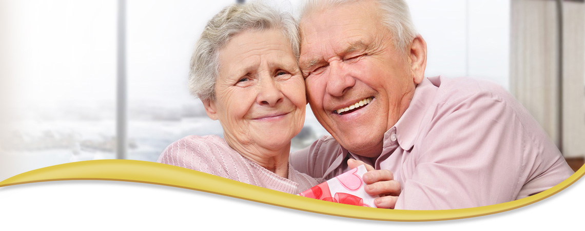 elderly couple smiling and laughing with their heads tilted together