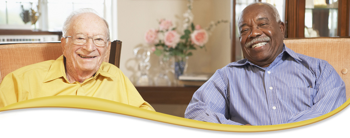two men seated smiling and conversing