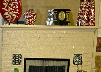 White brick fireplace with mantel decorate with red and white vases and a clock