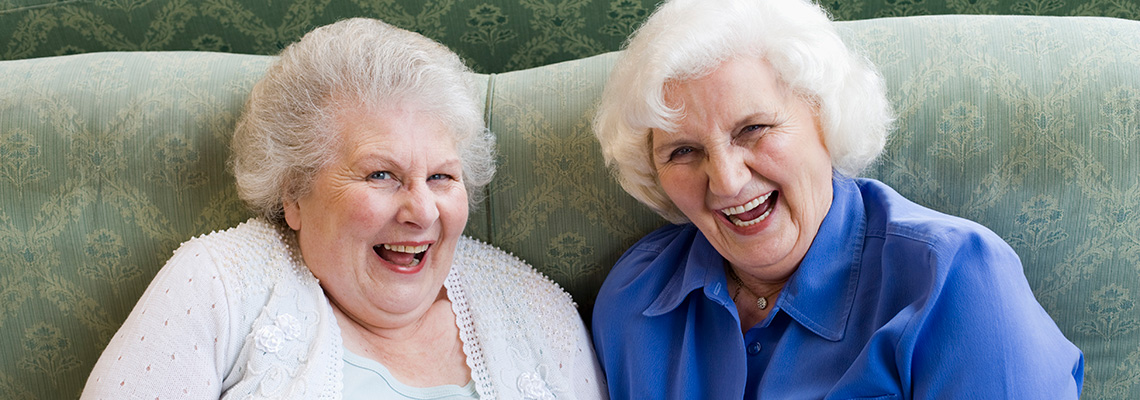two elderly women having a good laugh together