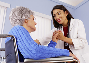 doctor leaning down to speak with a resident