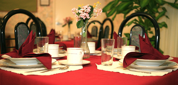 Resident dining area with the table set with flowers, silver wear and decorative table cover and napkins