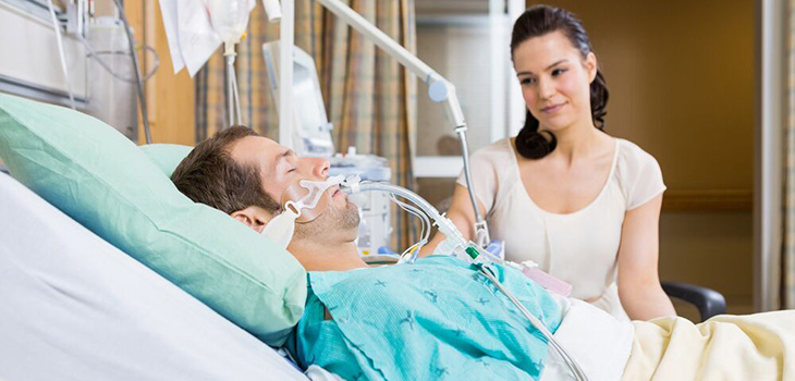 Man sleeping in hospital bed with woman looking over him