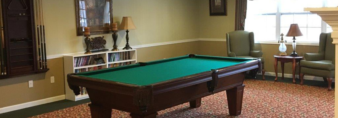 Pool table in an area with seating and books as well
