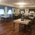 Resident dining room with covered tables and beautiful and clean wood floors